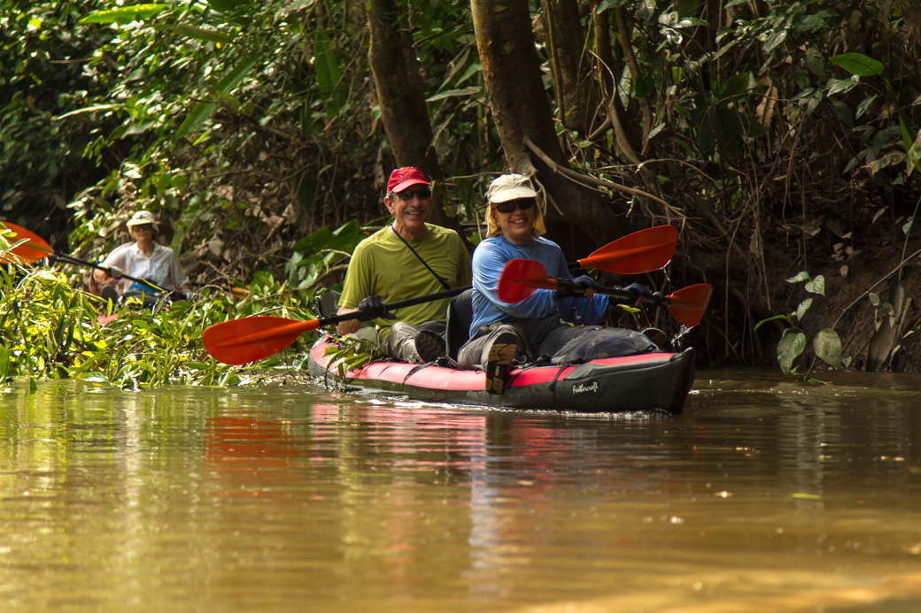 Kayakers negotiating a narrow portion of a side stream in the Amazon.
