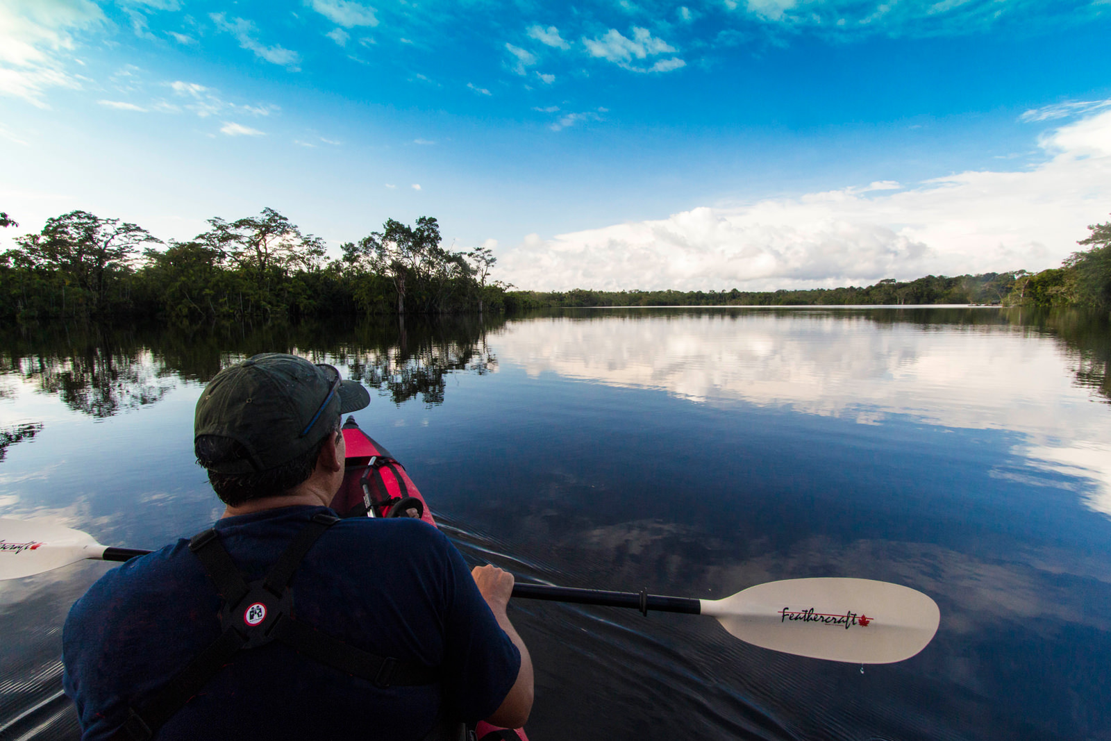 Kayaker on beautiful mirror calm Amazon lake