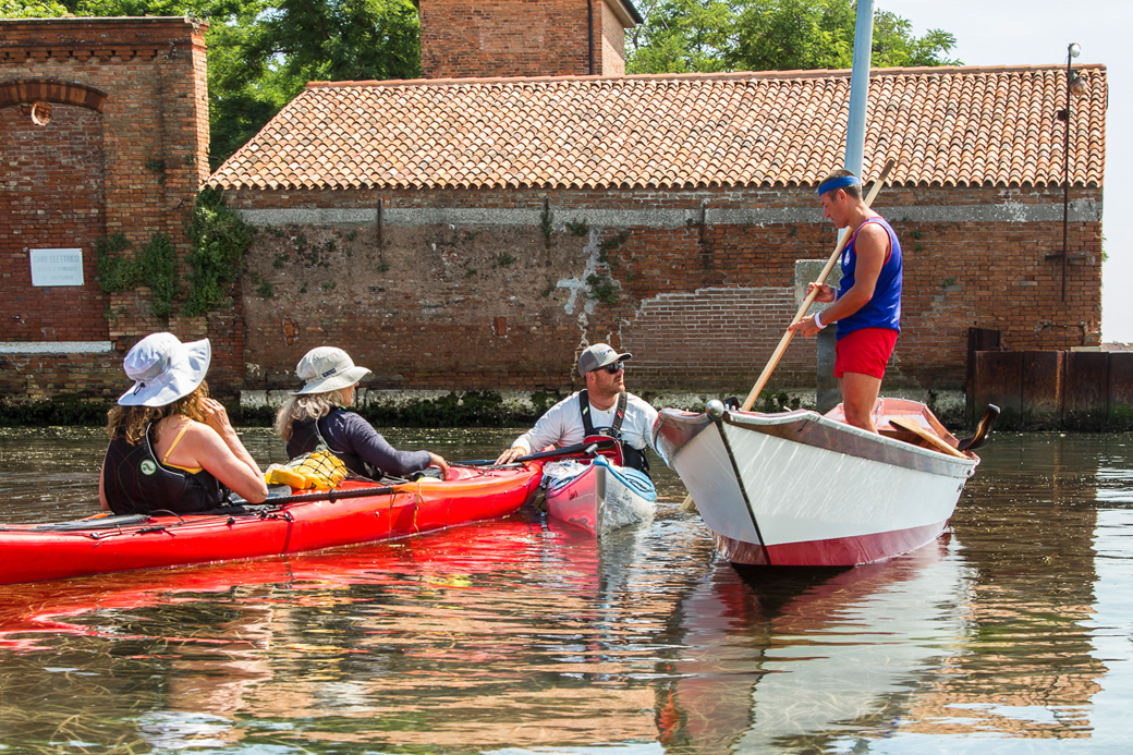 Kayakers meet a Venetian rower returning from a 15 km workout on the Laguna